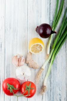 Odgórny widok warzywa jako pomidorowego czosnku cebulkowy imbir z cytryną na drewnianym tle z kopii przestrzenią
