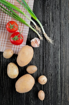 Odgórny widok warzywa jako pomidorowy kartoflany scallion i czosnek na drewnianym tle z kopii przestrzenią