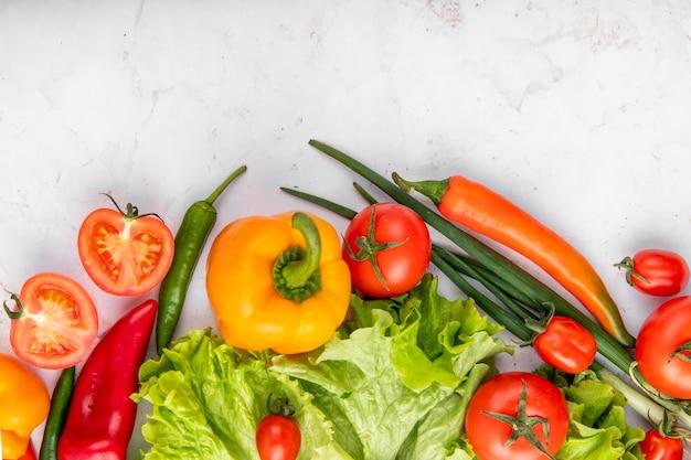Odgórny widok warzywa jako pomidory pieprzy brokuły i scallions na biel powierzchni