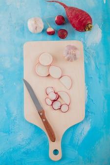 Odgórny widok warzywa jako rzodkiew i czosnek z nożem na tnącej desce na błękitnym tle