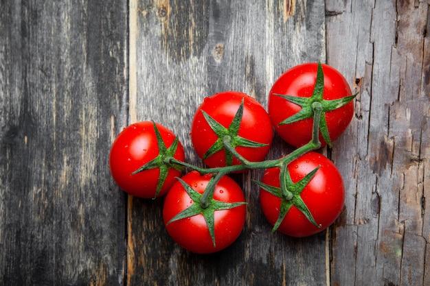 Odgórny widok wiązka pomidory na starym drewnianym tle. poziomy