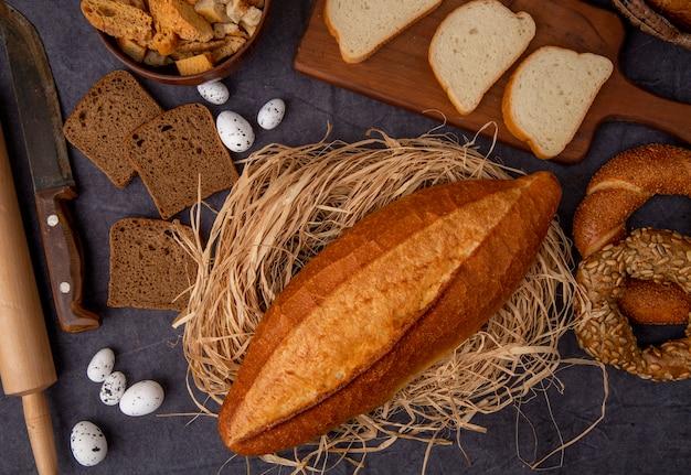 Odgórny widok wietnamczyka baguette na słomie z jajek nożowymi bagels białymi i żyto chlebami na wałkoni się tle