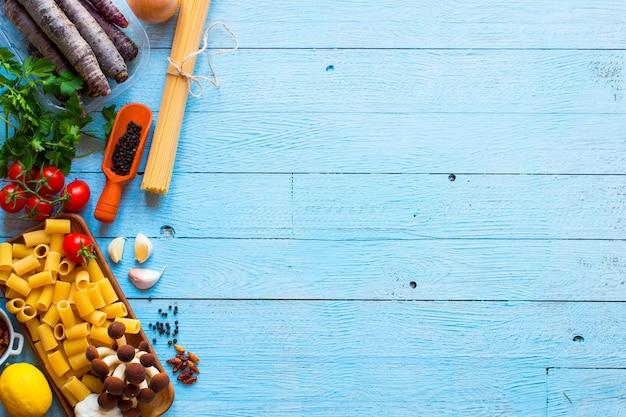 Odgórny widok włoscy składniki dla spaghetti nad drewnianym tłem.