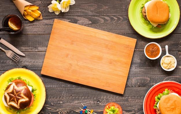 Odgórny widok wyśmienicie hamburger z warzywami na drewnianym tle.