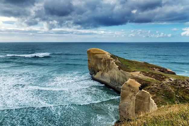 Odgórny widok wysoka piaskowata faleza i fala pacyficzny ocean przy tunel plażą, nowa zelandia
