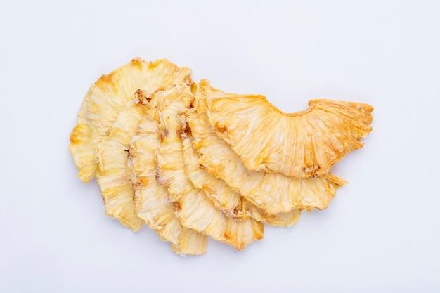Odgórny widok wysuszeni ananasów plasterki odizolowywający na białym tle