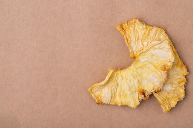 Odgórny widok wysuszeni ananasów plasterki odizolowywający na brown papieru tekstury tle z kopii przestrzenią