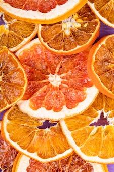 Odgórny widok wysuszeni pomarańcze i grapefruitowi plasterki układający na purpurowym tle