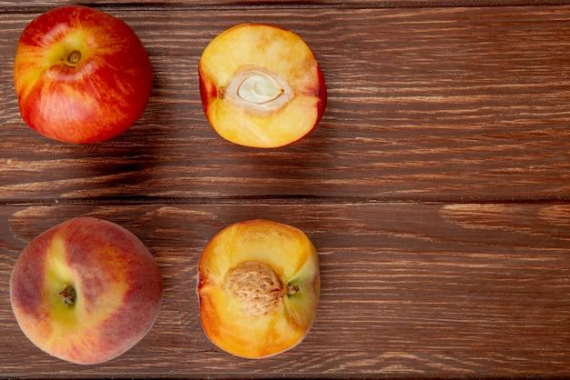 Odgórny widok wzór całe i przyrodnie rżnięte brzoskwinie na drewnianej powierzchni z kopii przestrzenią