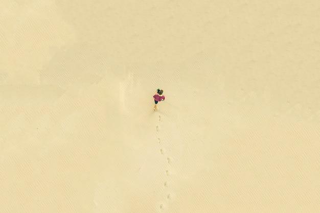 Odgórny widok z lotu ptaka młody samotny mężczyzna chodzi w pustyni na piasek teksturze. stracone pojęcie
