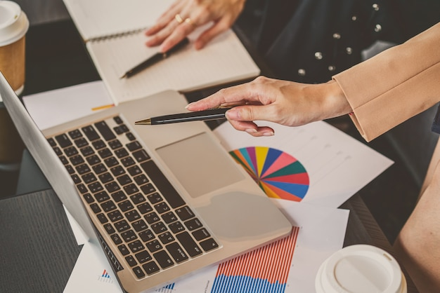 Odgórny widok zbliżenie azjatykci bizneswomany trzyma i pisze wskazywać laptop