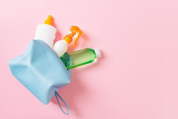 Odgórny widok żeńska kosmetyk torba pełno suncream kiść, sunsreen, sunblock i ciało płukanka i spf śmietanka na różowym tle z kopii przestrzenią. bezpośrednio powyżej. koncepcja jasnego lata