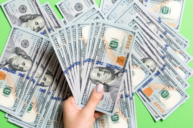 Odgórny widok żeńskie ręki kłama na stosie sto dolarowych banknotów.