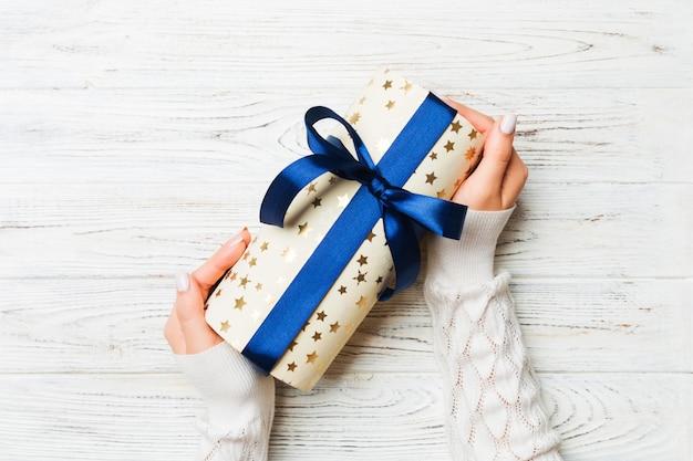 Odgórny widok żeńskie ręki trzyma boże narodzenia lub inny wakacyjnego handmade teraźniejszości pudełka pakunek w dłoniach, mieszkanie nieatutowy
