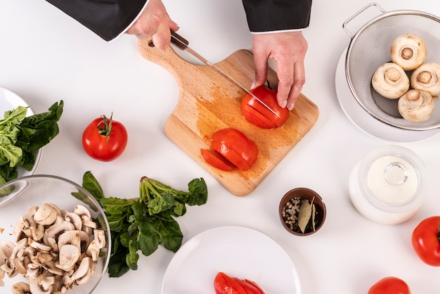 Odgórny widok żeńskiego szefa kuchni tnący pomidory