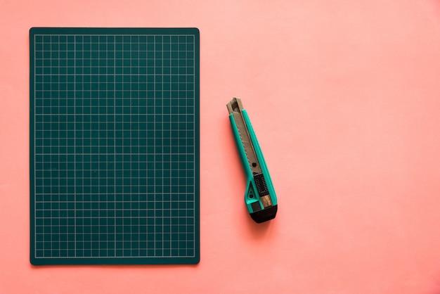 Odgórny widok zielona gumowa tnąca mata z zielonym krajaczem nad różowym koloru papieru tłem