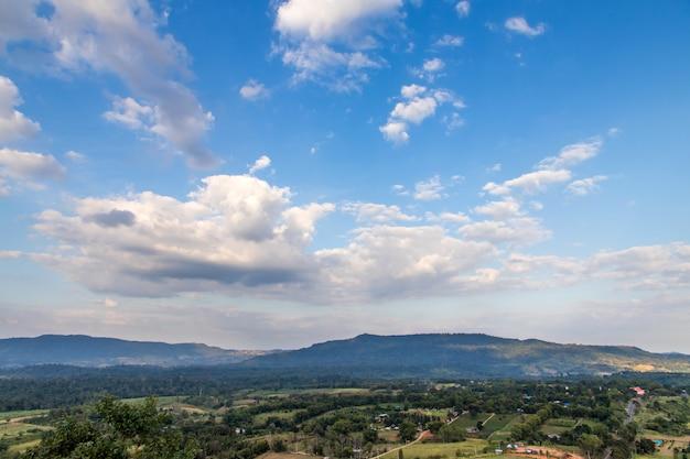 Odgórny widok zielone wzgórza, płotowa luksusowa trawa i niebieskie niebo z białymi chmurami