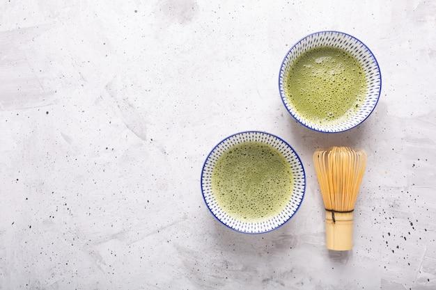Odgórny widok zielonej herbaty matcha w pucharze na betonowej powierzchni. orientacja pozioma, widok z góry