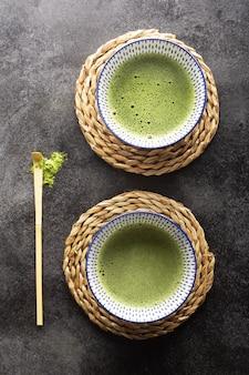 Odgórny widok zielonej herbaty matcha w pucharze na zmroku stole