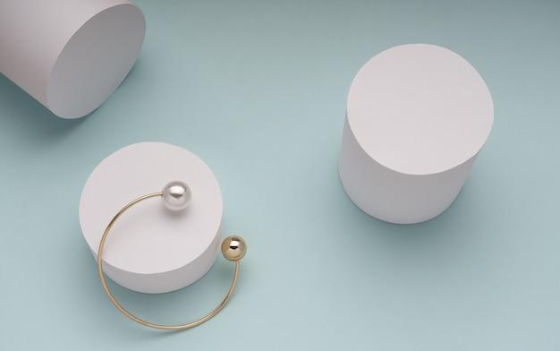 Odgórny widok złoty z perełkową bransoletką na białym cylindrze na zieleni
