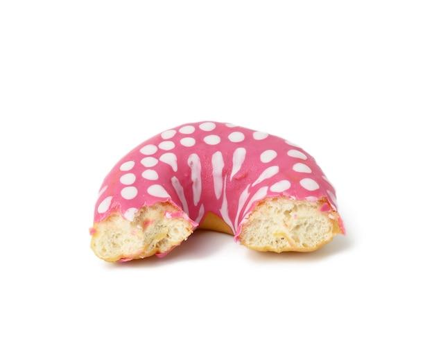 Odgryzione pączki z różowym lukrem na białej powierzchni