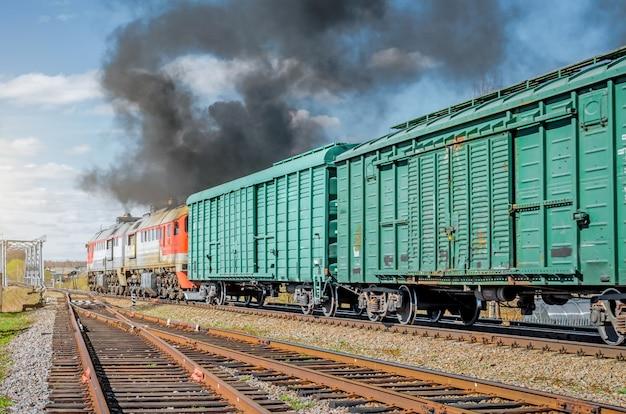 Odjazd kolei towarowej od starionu z czarnym dymem.
