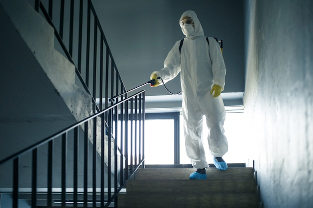 Odkażający pracownik sprzątający klatkę schodową w centrum handlowym za pomocą środka antyseptycznego, aby zapobiec rozprzestrzenianiu się covid-19. mężczyzna w skafandrze dezynfekującym spryskuje schody. koncepcja opieki zdrowotnej, kwarantanny i higieny.
