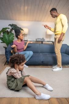 Odkrycie kart. ciemnoskórzy młodzi rodzice rozgrywający pojedynek i córeczka zakrywająca uszy rękami siedzącymi na podłodze w domu
