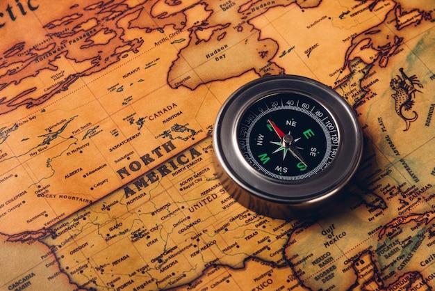 Odkrycie starego kompasu na mapie świata antycznego papieru vintage