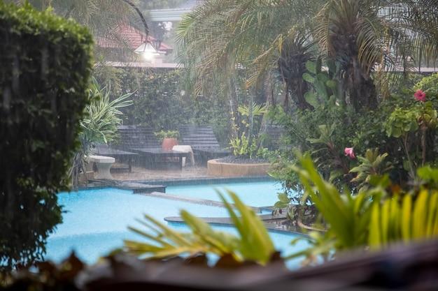 Odkryty basen w tropikalnym ogrodzie hotelu w deszczu.