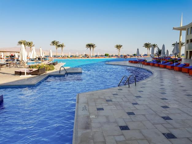 Odkryty basen z mnóstwem leżaków w letnim hotelu na plaży?