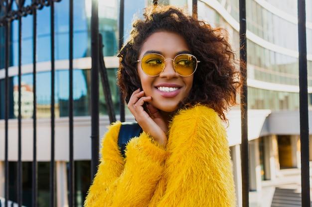 Odkryty bliska portret szczęśliwa dziewczyna z plecakiem stojącym na miejskich