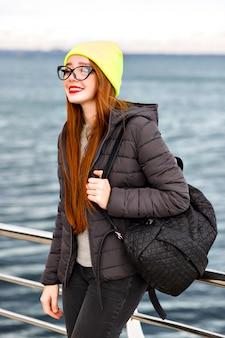 Odkryty hipster moda portret młodej ładnej kobiety z długimi rudymi włosami, pozuje blisko morza, podróżuje samotnie z plecakiem, zimna pogoda, stylowy zimowy wygląd ulicy, czapka, kurtka, sweter.