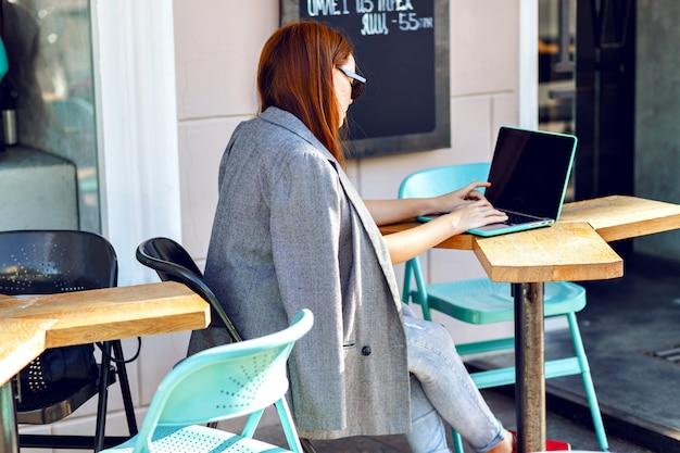 Odkryty miasto moda portret młodej bizneswoman pracuje w kawiarni na tarasie w słoneczny dzień, dorywczo stylowy strój, miętowe detale, używając swojego laptopa, przerwa w kawiarni, koncepcja biznesowa.