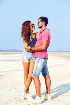 Odkryty moda portret młodej ładnej pary zakochanych pozuje na niesamowitej plaży, ubrana w jasne stylowe ubranie i okulary przeciwsłoneczne, ciesz się wakacjami w pobliżu oceanu.