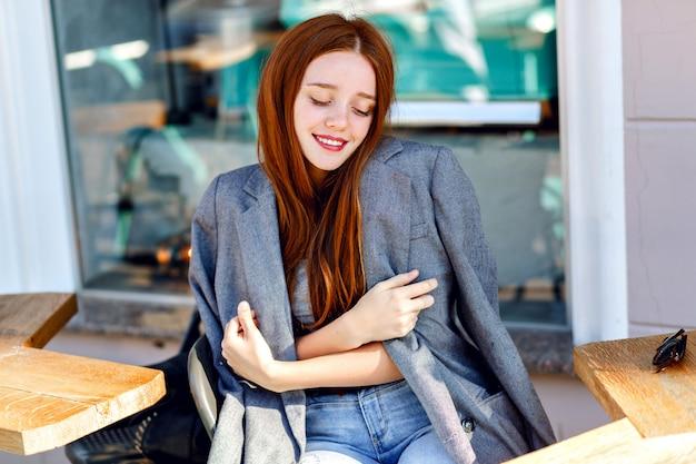 Odkryty moda portret stylowej rudej kobiety, pozowanie w kawiarni na tarasie, w słoneczny dzień, na sobie kurtkę chłopaka, jasne, świeże kolory.