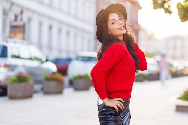 Odkryty moda uliczny wizerunek uwodzicielskiej brunetki w jesiennym stroju casual spaceru w słonecznym mieście. czerwony sweter z dzianiny, czarna modna czapka, skórzana spódnica.