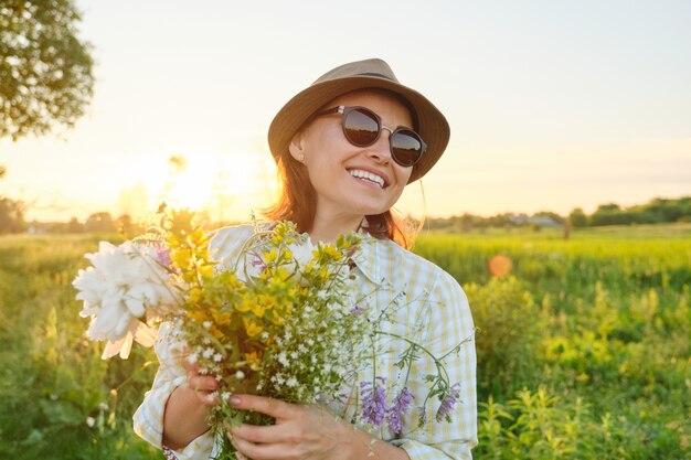 Odkryty portret dojrzałej szczęśliwej uśmiechniętej kobiety z wiosennych kwiatów, kobiety w kapeluszu okulary