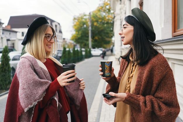 Odkryty portret dwóch rozmawiających koleżanek. dziewczyny w zwyczajnych ciepłych strojach i okularach spacerujące po mieście w zimnych porach roku i pijące kawę na miejskiej ulicy. miejski styl życia, koncepcja przyjaźni.