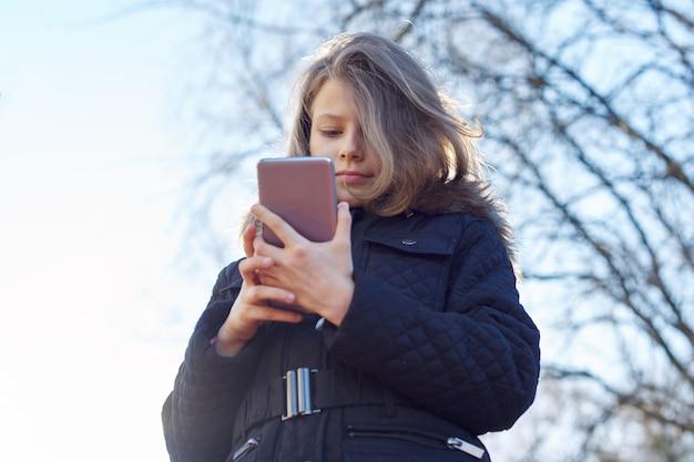 Odkryty portret dziecko dziewczynka 8, 9 lat ze smartfonem, wiosna dziewczyna w kurtce.