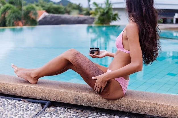 Odkryty portret kobiety w różowym bikini w spa przy basenie trzymając scrab kawy