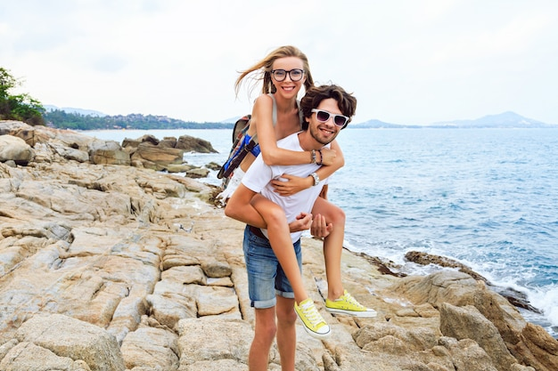 Odkryty portret młodej pięknej pary zakochanych pozuje i bawi się na ładnej kamiennej plaży, stonowanych kolorach.