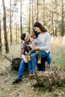 Odkryty portret szczęśliwej rodziny kaukaskiej, ojca, matki i małego chłopca, noszący stylowe ubranie, siedzący na kłodzie w sosnowym jesiennym lesie i uśmiechający się do kamery