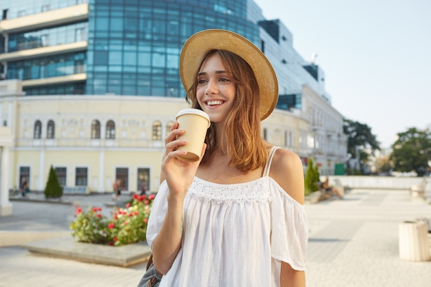 Odkryty portret szczęśliwej ślicznej młodej kobiety nosi stylowy letni kapelusz i białą sukienkę, czuje się zrelaksowany, uśmiecha się i pije kawę na wynos na ulicy w mieście