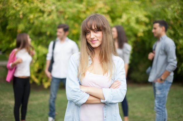 Odkryty portret uśmiechnięta młoda kobieta przed grupą studentów