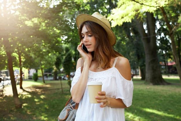 Odkryty portret uśmiechniętej uroczej młodej kobiety nosi stylowy kapelusz i białą letnią sukienkę, czuje się szczęśliwa, spaceruje i pije kawę na wynos na ulicy w mieście