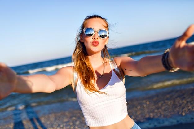 Odkryty portret zabawnej szczęśliwej dziewczyny podróżującej samotnie nad ocean, robiącej selfie na plaży, szczęśliwe pozytywne emocje, lustrzane okulary przeciwsłoneczne, biały top i plecak, radość, ruch.