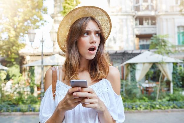 Odkryty portret zdumionej, zszokowanej młodej kobiety nosi stylowy kapelusz i białą letnią sukienkę, czuje się oszołomiony, używając telefonu komórkowego i spacerując po starym mieście