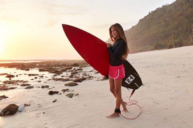 Odkryty poziome strzał szczupła piękna kobieta w spodniach, stoi w pobliżu klifu na piaszczystym brzegu
