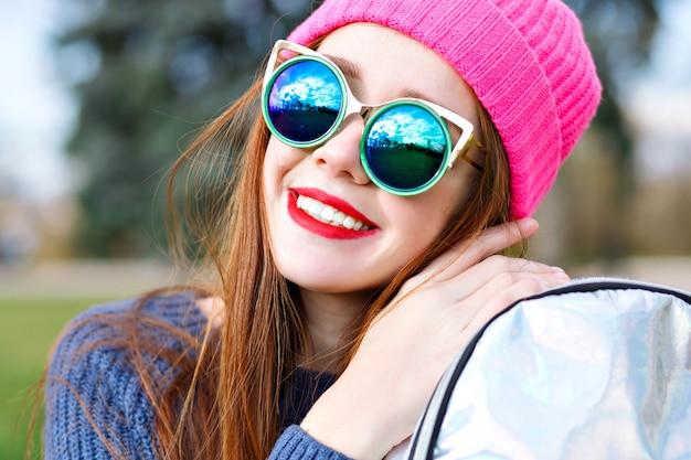 Odkryty pozytywny portret mody oszałamiającej pięknej rudej kobiety, pozuje w parku miejskim, w kapeluszu hipster i pogodzie, modne luksusowe okulary przeciwsłoneczne, młodzież, wakacje, czerwone usta, pastelowe kolory.